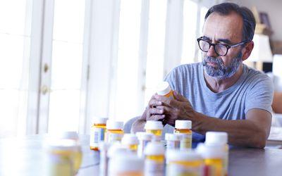 Man Sitting At Table Sorting Through Prescrption Medications