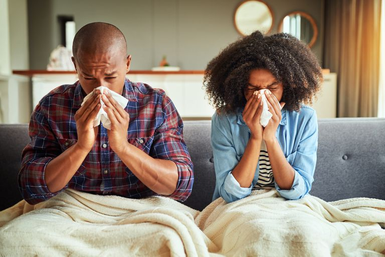 Two people sneezing in bed