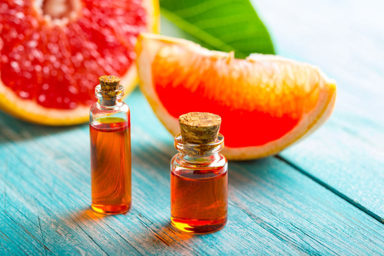 Grapefruit next to grapefruit essential oil