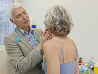 Doctor checking woman's lymph nodes