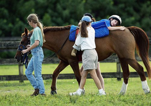 An autistic boy with cerebral palsy undergoing horse therapy