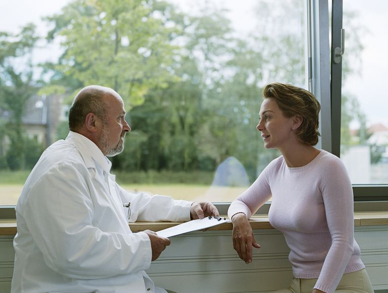Male doctor talks with female patient in front of a large window