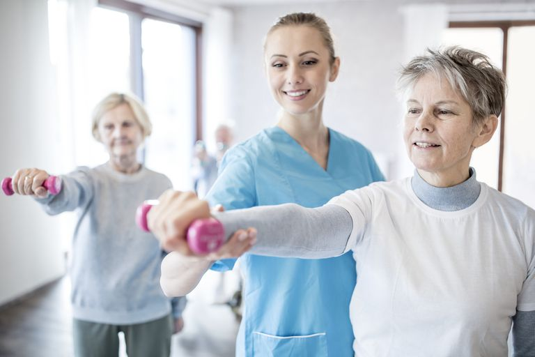 Senior woman holding hand weight, physiotherapist helping.