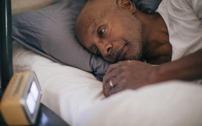 Man looks at alarm clock.
