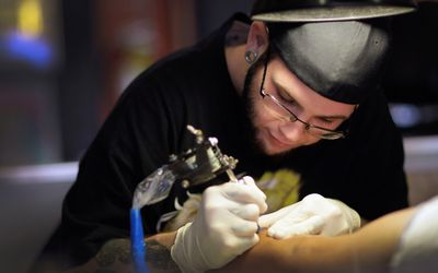 a man giving a tattoo on someone's arm