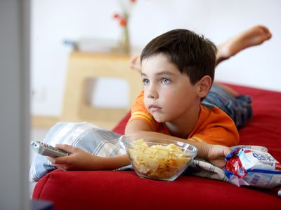 Boy eating junk food watching tv