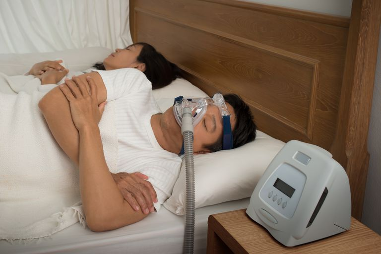 Man Wearing CPAP Mask While Suffering From Sleep Apnea By Woman On Bed At Home