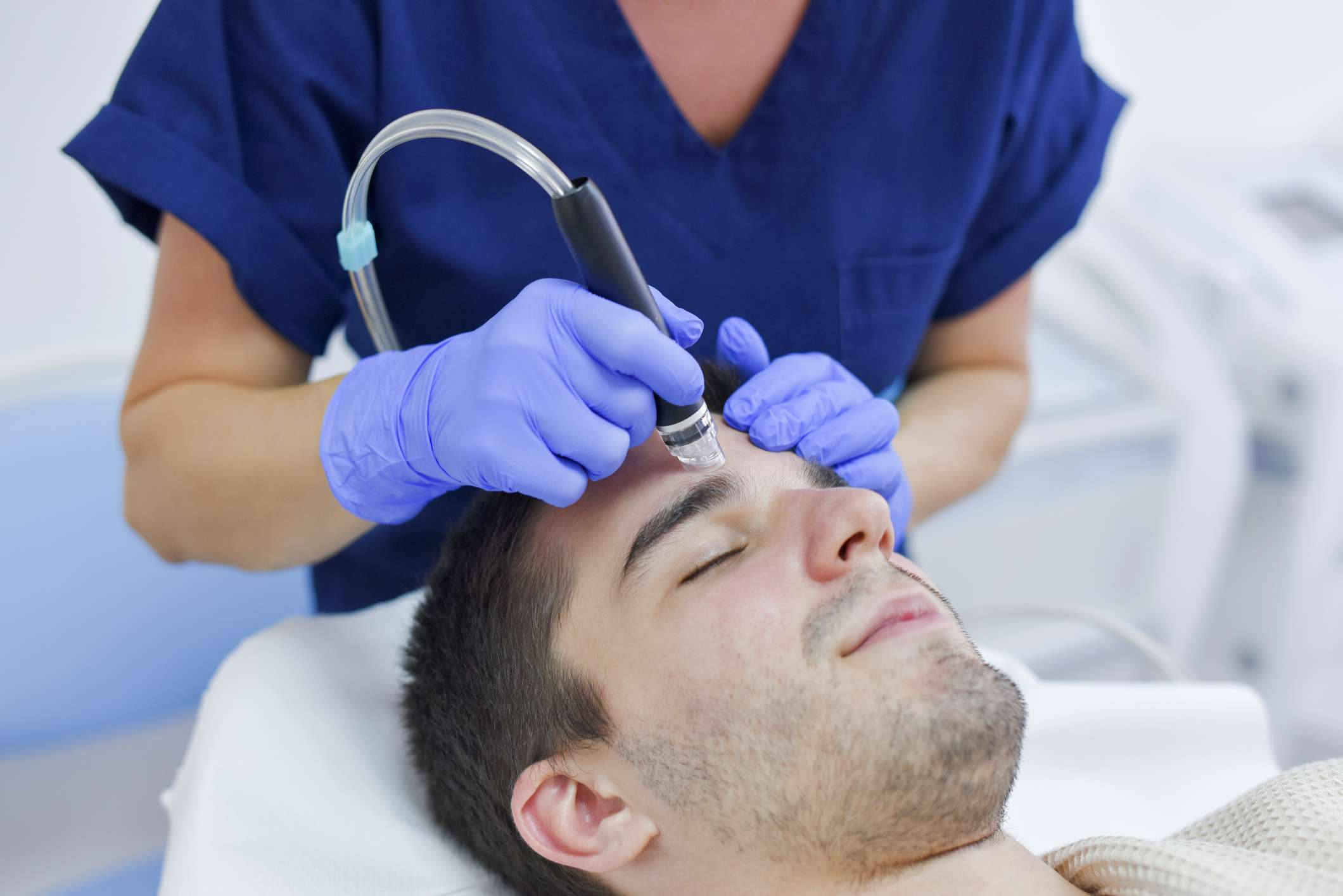 Dermatologist performing treatment on patient
