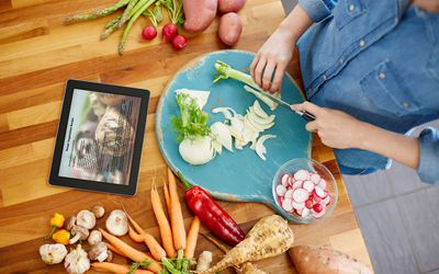 woman cutting vegetables and looking at a recipe