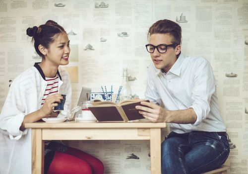 Young man and woman sitting in a cafe looking at a book