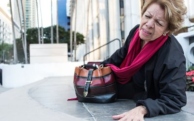Photo of an elderly woman falling down.