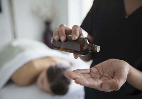 Massage therapist pouring oil into her hand