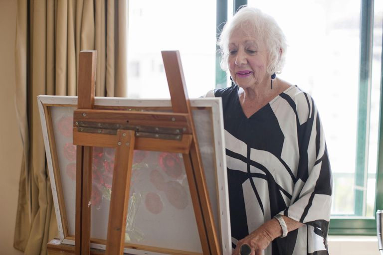 Senior women painting art canvas in retirement villa