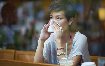 Woman blowing her nose inside cafe