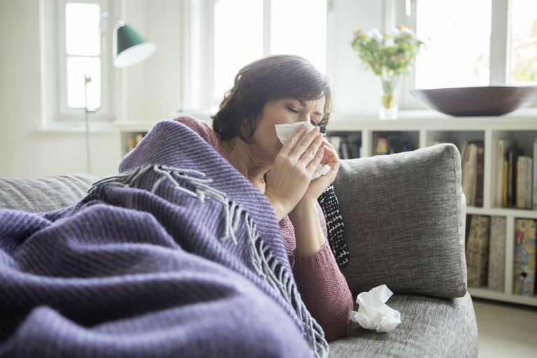 Woman with the flu laying on the couch