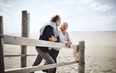 Senior couple standing on boardwalk on the beach