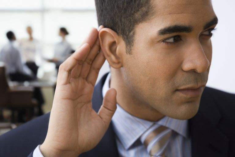 Mixed race businessman cupping ear to listen