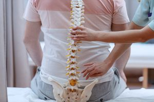 Nurse holding spine model against the patients backs. Clinic interior