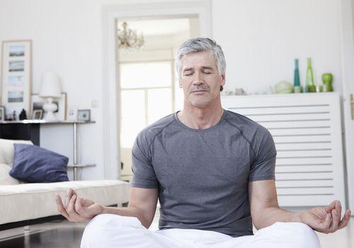 Mature man meditating in his living room
