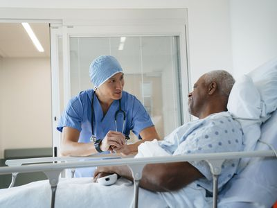 Surgeon talking with senior patient lying on bed in hospital ward