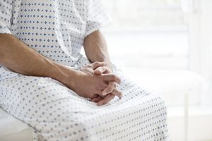 Man sitting on hospital bed with hands folded