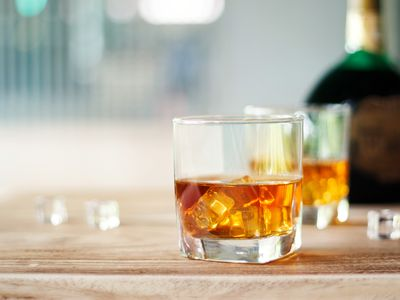 Whisky in two glasses and bottle on a wooden table background.