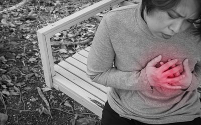 woman on bench holding breast in pain