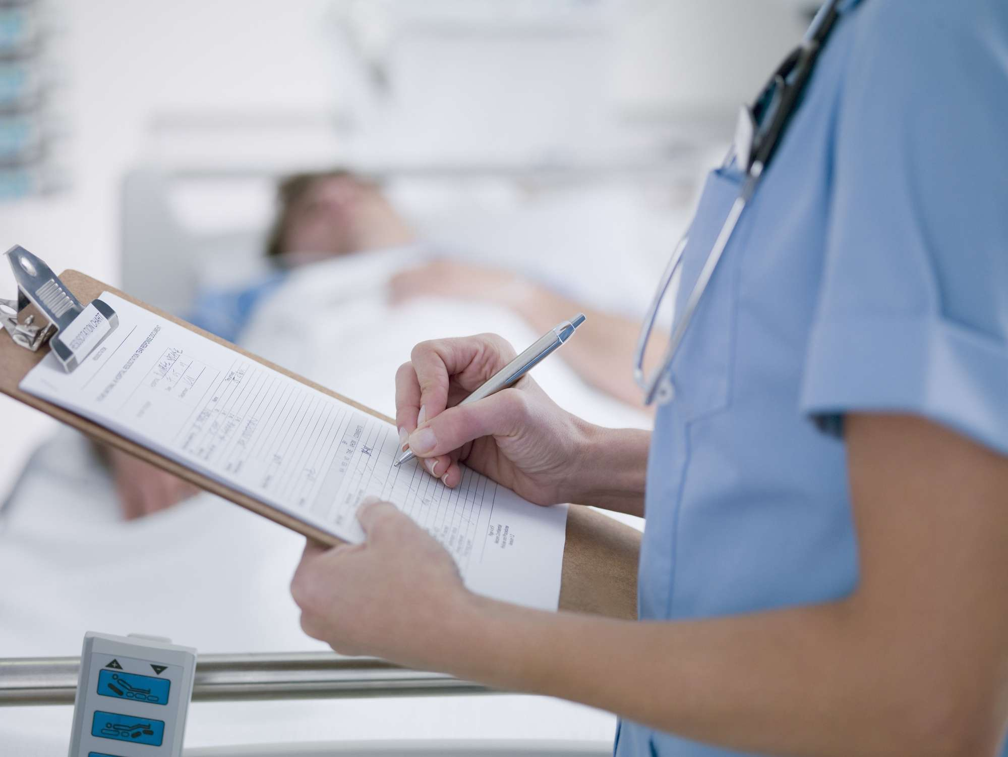Nurse writing on clipboard and patient with bacteremia in hospital bed in the background