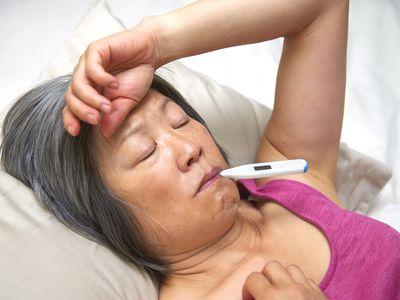 Person ill in bed, taking temperature