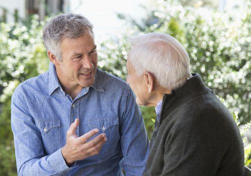 man talking to older man