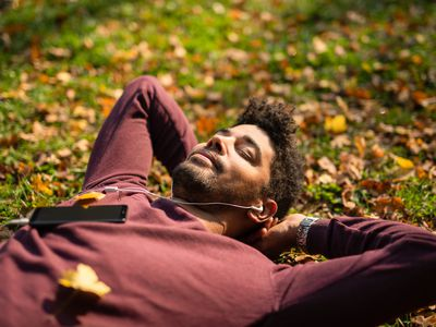 Relaxed young man laying on ground and listening to music on autumn day.