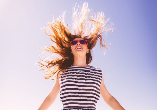 Woman jumping with sunglasses on