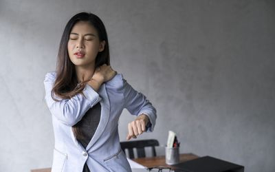 Office syndrome concept.Tired exhausted Asian young businesswoman work hard shoulder pain after working on computer laptop for a long time
