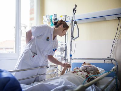 Nurse holding the hand of someone in hospice