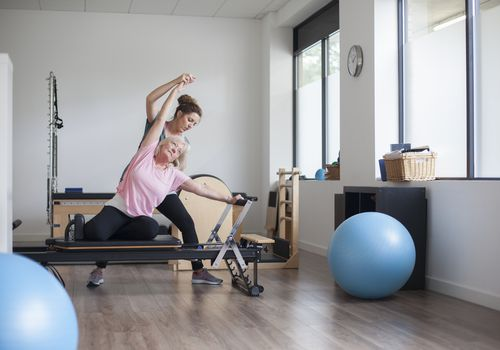 Instructor helping mature woman on the Pilates reformer