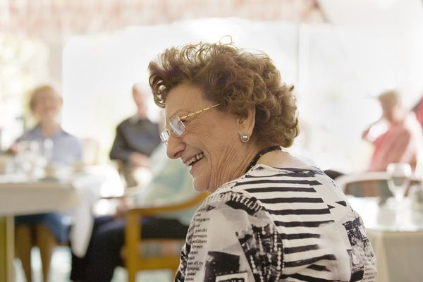 Elderly Woman in Nursing Home Dining Room Smiling