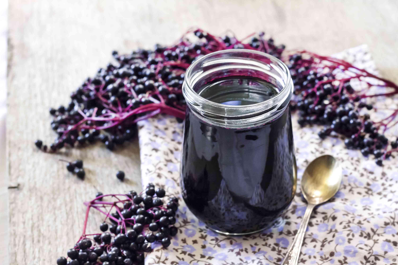 Homemade black elderberry syrup in glass jar