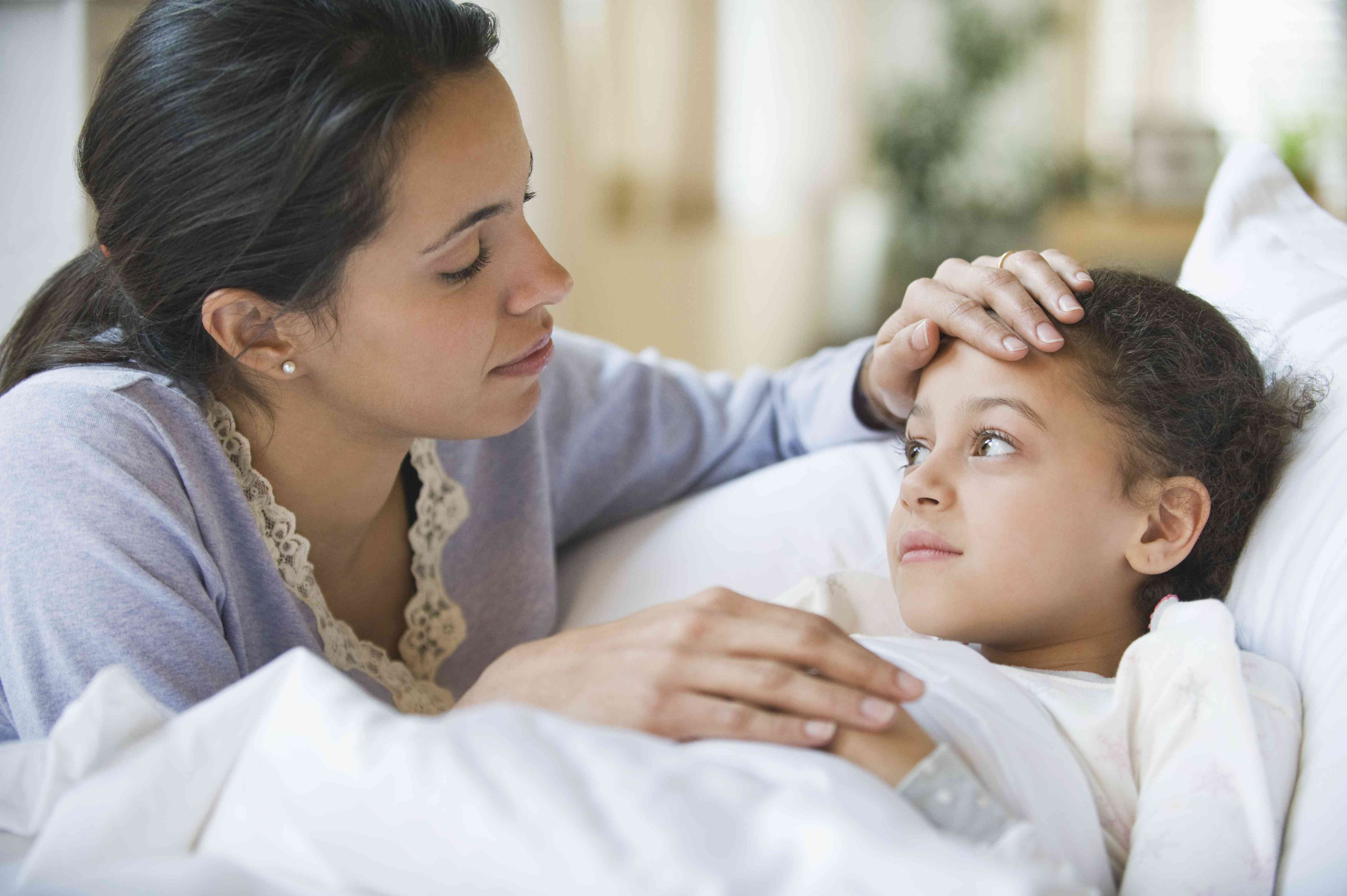 Hispanic mother comforting sick child