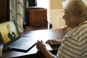 Senior woman using laptop to video chat with nurse during telehealth visit.