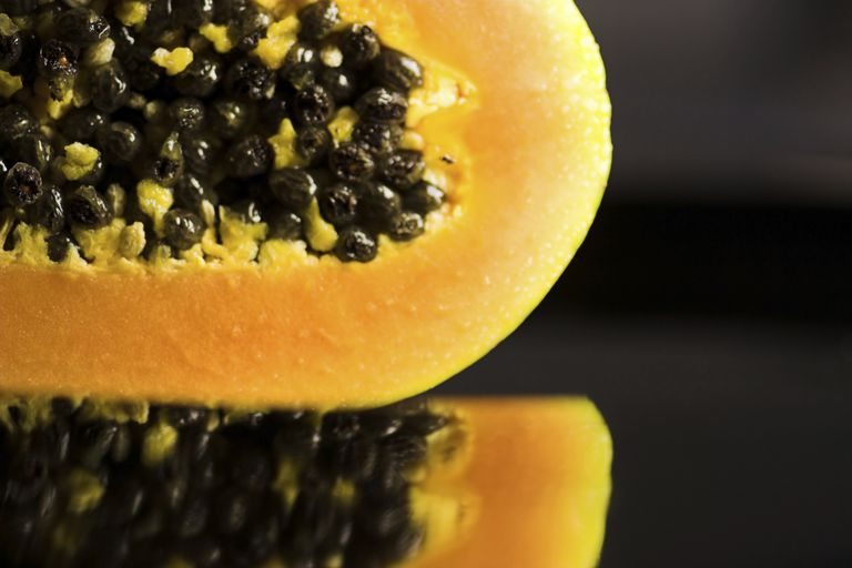 close up of a halved papaya on a reflective surface