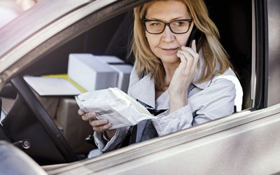 woman with small package in car