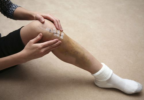 person sitting on the floor with a healing incision on their knee
