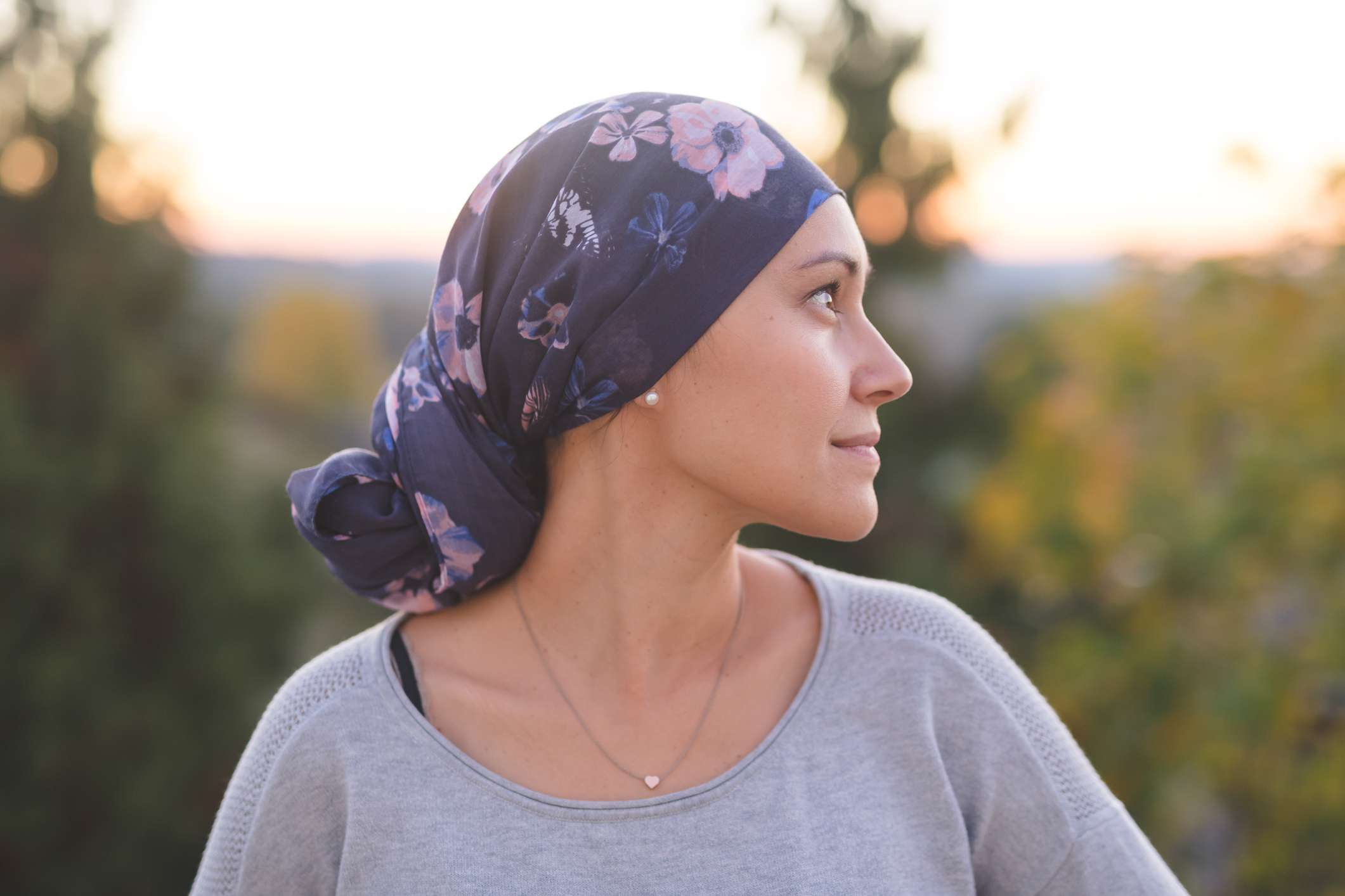 Ethnic woman battling cancer stands outside