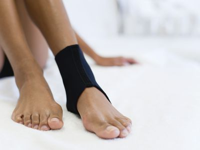 Woman's feet with ankle in black brace