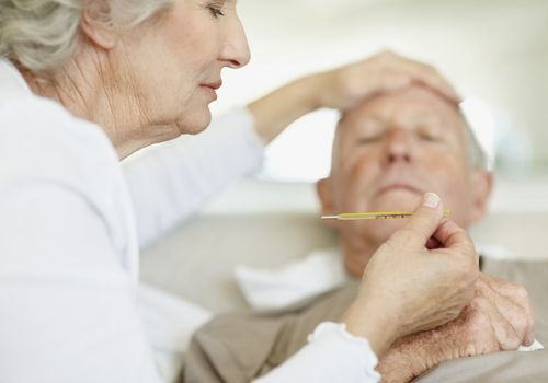 older woman taking older man's temperature