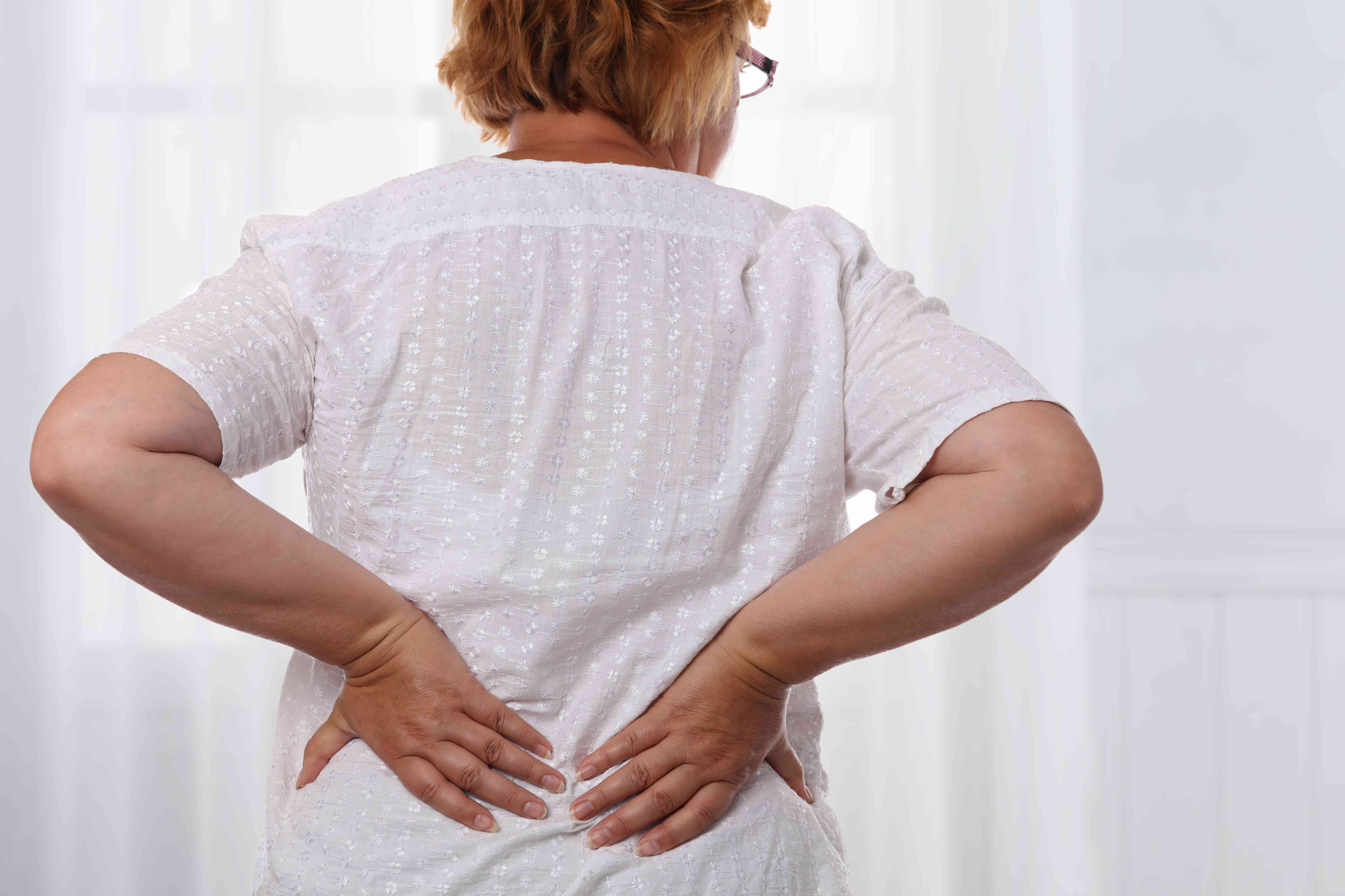 Senior woman suffering from low back pain. Chiropractic, osteopathy, Physiotherapy. Alternative medicine, pain relief concept.