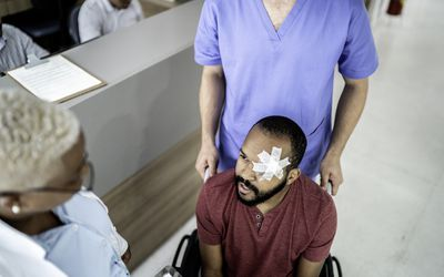 Patient after eye surgery talks to doctor