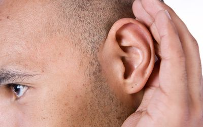 A man cupping his ear to hear clearly