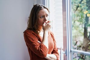 Woman looking worried out the window