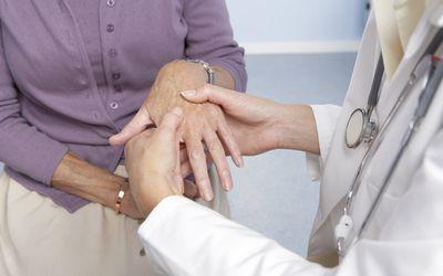 Rheumatoid arthritis, general practitioner examining patient and hand for signs of rheumatoid arthritis